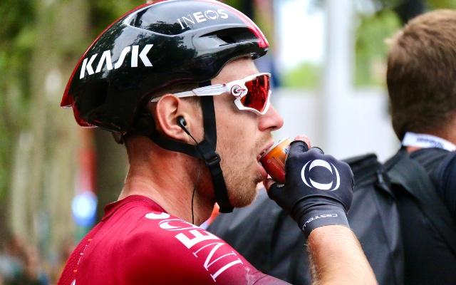 Ciclista del equipo INEOS bebiendo un refresco.